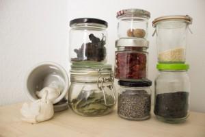 Zutaten in Gläsern: Knoblauch, Lohrbeer, getrocknete Chipotle Chillis, getrocknete Tomaten, Lavendel, Muskatnüse, heller und dunkler Sesam